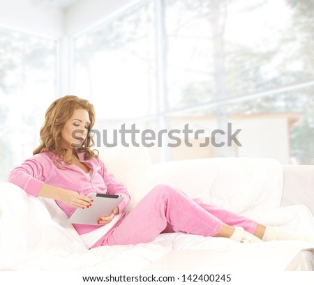 Young, beautiful and happy woman is reading in the home interior - stock photo