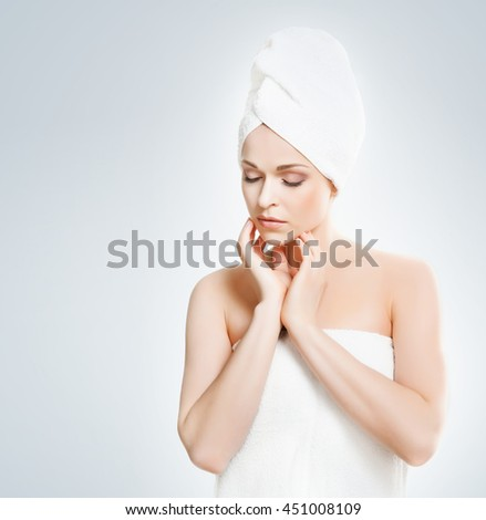 Young, beautiful and natural woman wrapped in towel over grey background - stock photo