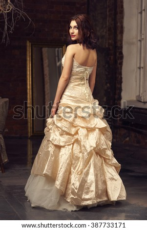 Young beautiful and pretty bride full length portrait in wedding dress in grunge interior