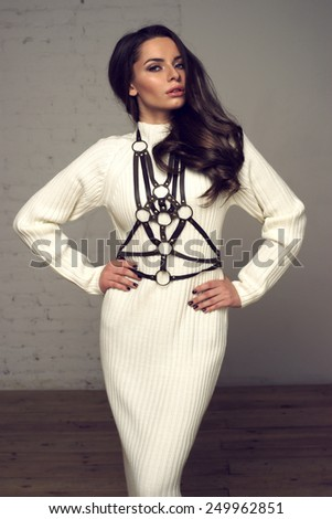 Young beautiful and pretty stylish girl with long dark hair posing in long knitted white dress and brown leather harness belt. Sexy fashionable portrait of sexy female model wearing  - stock photo