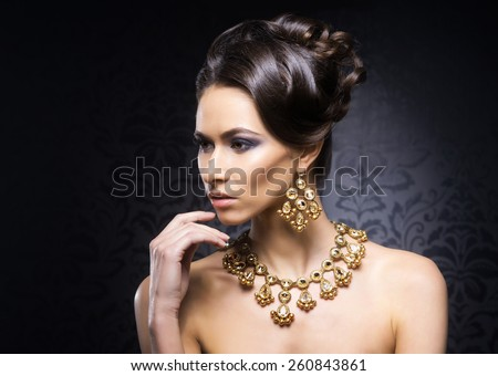 Young, beautiful and rich woman in jewels of gold and stones over luxury background  - stock photo