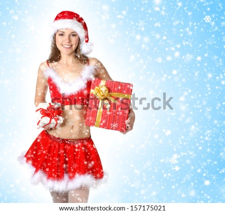 Young, beautiful and sexy Santa over the Christmas background (blue with snowflakes) - stock photo