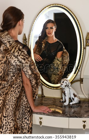 Young, beautiful and sexy woman in black stylish lingerie and fur coat looking in the mirror. - stock photo