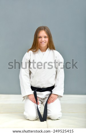 young, beautiful and successful karate women stretch out and relax before training
