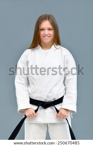 young, beautiful and successful karate women stretch out and relax before training - stock photo