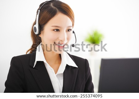 young beautiful asian businesswoman with headset in office - stock photo
