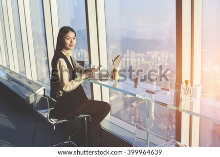 Young beautiful Asian female student with mobile phone in hands is looking at camera, while is sitting with laptop computer in co-working cafe with view of a business district outside the window - stock photo