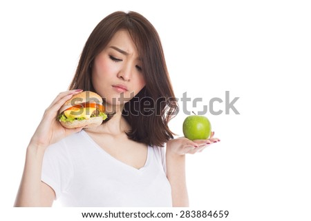 Young beautiful asian girl making choice between hamburger and a green apple, healthy eating and lifestyle  concept.