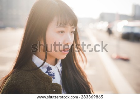 young beautiful asian hipster woman in the city - living town during sunset in backlit - stock photo