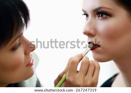 Young beautiful asian woman applying make-up by make-up artist, focus on lips - stock photo