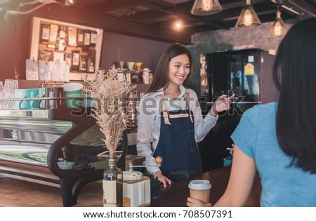 Young beautiful Asian woman barista wear blue apron talking to customer at bar counter in coffee shop with smile face.Concept of cafe and coffee shop small business.Vintage tone