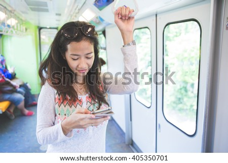 young beautiful asian woman browsing and typing messages in a public bus - stock photo