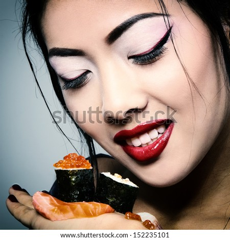 Young beautiful asian woman eating sushi, toned image and noise added - stock photo