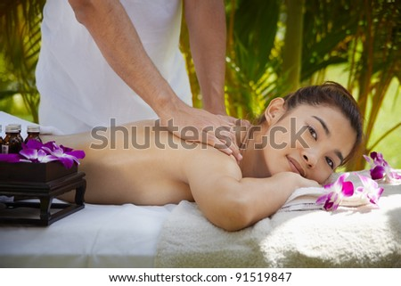 Young beautiful asian woman gets massage and beauty treatment in luxury resort. Side view - stock photo