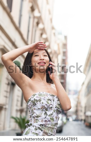 Young beautiful asian woman looking up smiling and talking using mobile phone urban outdoor spring dressing - stock photo