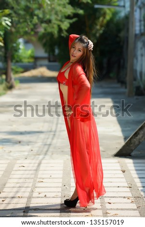 Young beautiful Asian woman naked. Wearing red transparent robe and bra no underpants, standing posing outdoor. - stock photo