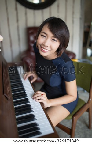 Young beautiful asian woman playing piano at home - stock photo
