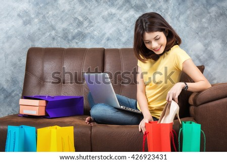 Young beautiful asian woman sitting on sofa shopping online with shopping bags at home. - stock photo