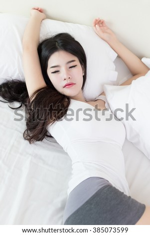 young beautiful asian woman sleeping on bed - stock photo