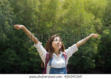Young beautiful asian woman stretch enjoying with fresh air in the forest - stock photo