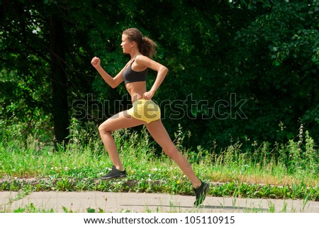 Young beautiful athlete woman jogging in summer park - stock photo