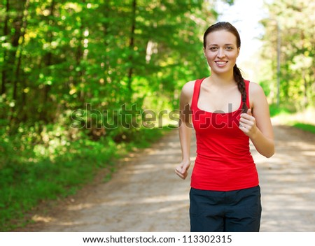 Young beautiful athlete woman jogging outdoors in park - stock photo