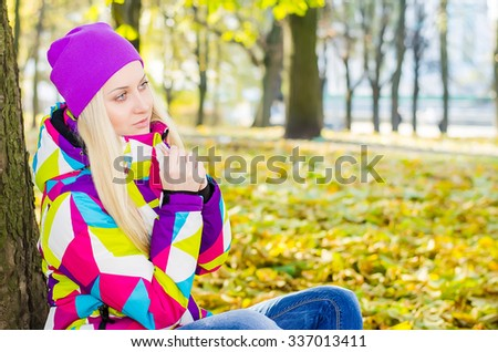 Young beautiful athletic girl sitting near a tree in a park in the yellow foliage. Jeans, colored jacket, purple hat. Look. Autumn, cold