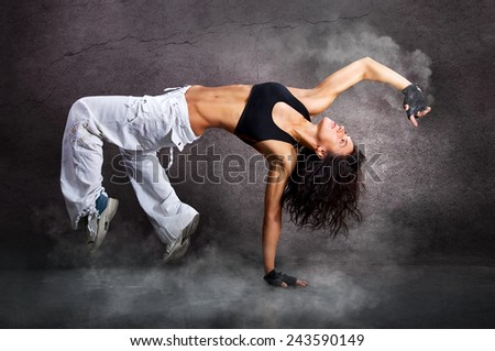 Young beautiful athletic woman jumping dancing modern dance hip-hop on wall background with smoke