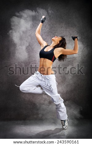 Young beautiful athletic woman jumping dancing modern style dance hip-hop on studio on wall background with smoke - stock photo