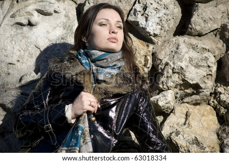 Young beautiful attractive fashionable woman posing against old stone wall outdoor near Kremlin Moscow Russia
