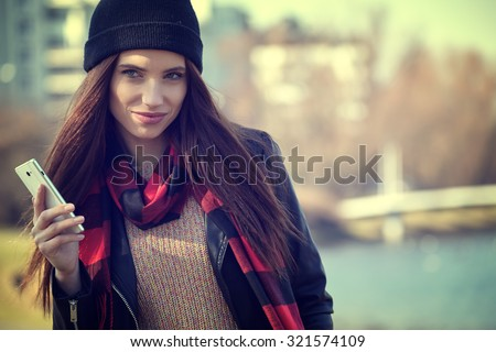 Young beautiful autumn woman with cell phone - stock photo
