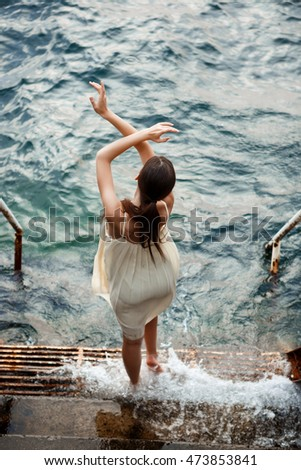 Young beautiful ballerina dancing and posing outside, sea background.
