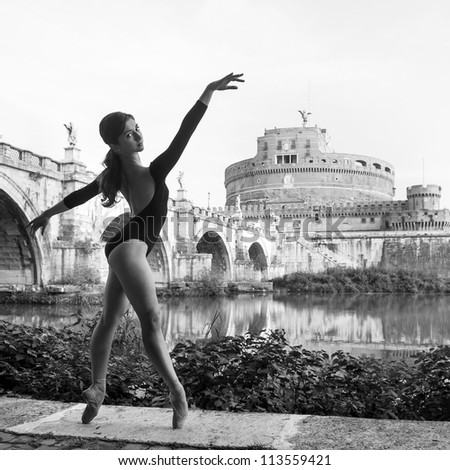 Young beautiful ballerina dancing out in Tevere riverside with castel Santangelo in the background in Rome, Italy. Black and white image. Ballerina Project. - stock photo