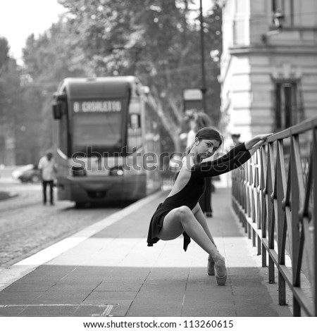 Young beautiful ballerina dancing out in the street in Rome, Italy. Black and white image. Ballerina Project. - stock photo
