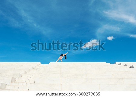 Young beautiful ballerina dancing outdoors in a modern environment with blue cloudy sky background. Ballerina Project. Filtered image. - stock photo