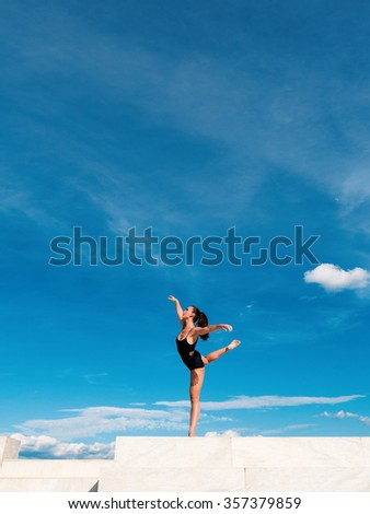 Young beautiful ballerina dancing outdoors in a modern environment with blue sky. Ballerina Project. - stock photo