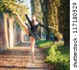 Young beautiful ballerina dancing outdoors in a narrow path. Ballerina Project. - stock photo