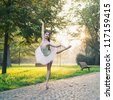 Young beautiful ballerina dancing outdoors in a park. Ballerina Project. - stock photo