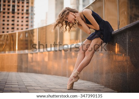 Young beautiful ballerina in black dress and pointe shoes dancing outdoors in a modern environment. Ballerina Project.