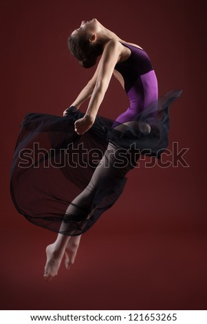 young beautiful ballerina in mid-air with a black cloth