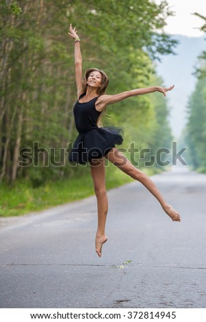 Young beautiful ballerina jumping outdoors in a parkway with trees.  - stock photo