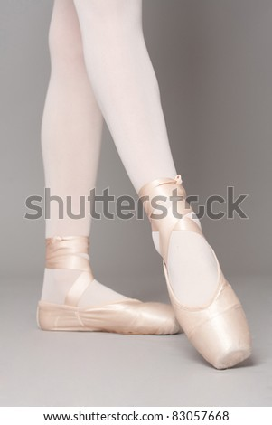 young beautiful ballerina posing in front of gray studio background - stock photo