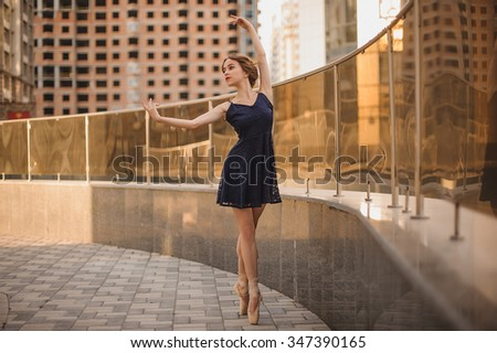 young beautiful Ballet dancer ballerina with hair up in black dress outdoors - stock photo
