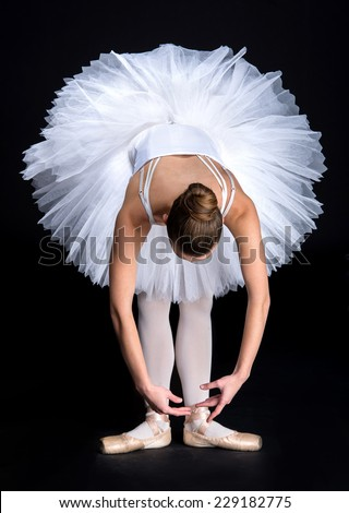 Young beautiful ballet dancer is posing on a studio black background. - stock photo