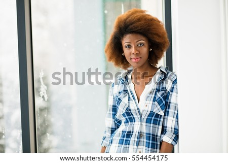 young beautiful black woman in checkered shirt standing next to a window