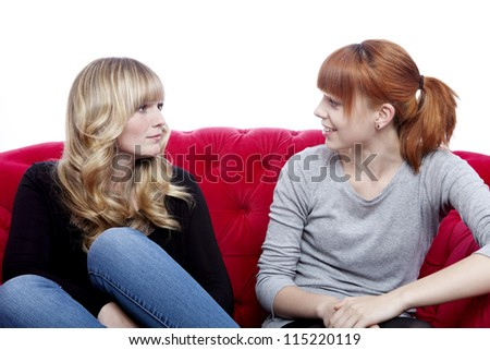 young beautiful blond and red haired girls talking and sitting on red sofa in front of white background - stock photo