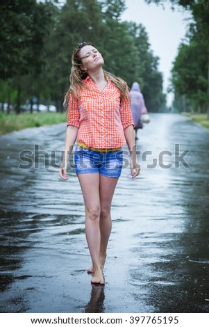 Young beautiful blond caucasian girl in shorts and shirt walking in the park in the summer warm rain barefoot through the puddles. Have fun and enjoy. Falling rain. Raindrops. Wet clothes, wet hair - stock photo