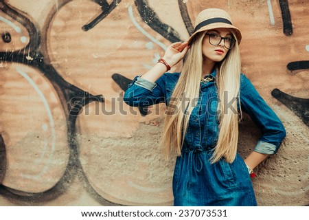 young beautiful blond girl stands near a wall graffiti - stock photo