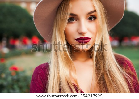 young beautiful blond girl with red lipstick in her big bright eyes and make it in a bright coat and red dress with black handbag posing on the streets of Italy, Spain, the setting sun trendy clothes  - stock photo