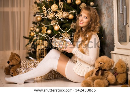 Young beautiful blond girl, woman in a beautiful room with a Christmas tree, a Christmas tree, a girl with gifts, gold tree, golden hair, happy woman new year, Teddy bear, beige colors - stock photo